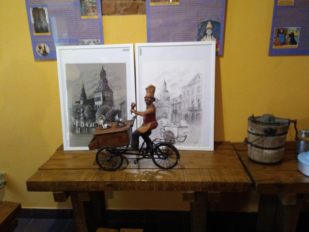 Widok stołów z figurką sprzedawcy lodów, grafikami, drewnianą maszyną do produkcji lodów, na ścianie wiszące tablice