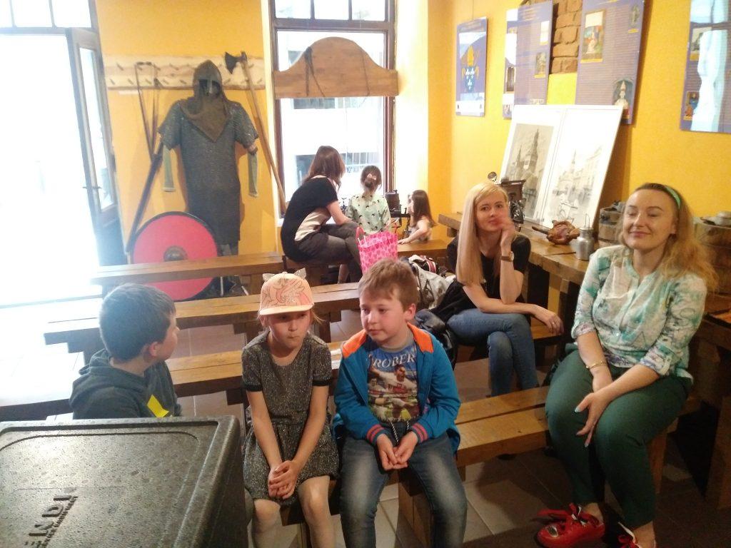 Siedzące osoby na ławach, z tyłu widoczny manekin w stroju średniowiecznego woja oraz okno wystawowe
