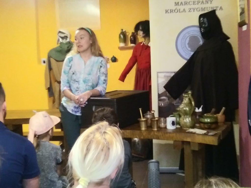 Stojąca osoba oparta o stół z naczyniami glinianymi, z tyłu widoczne manekiny w stroju średniowiecznym, nowożytnym oraz w habicie mnicha
