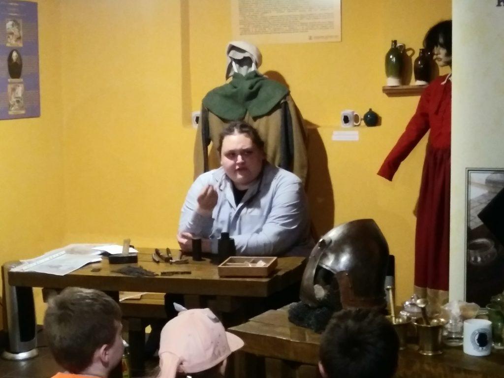 Siedząca osoba za stołem z akcesoriami rzemieślniczymi, z tyłu widoczny manekiny w stroju średniowiecznym oraz nowożytnym, z boku znajduje się hełm rycerski