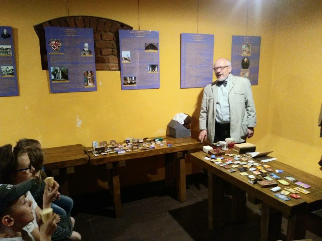Stojąca osoba na tle stołów z kolekcją pudełek po zapałkach, z tyłu widoczny manekin w stroju średniowiecznym, na ścianie wiszące tablice, z przodu widoczne są twarze siedzących osób