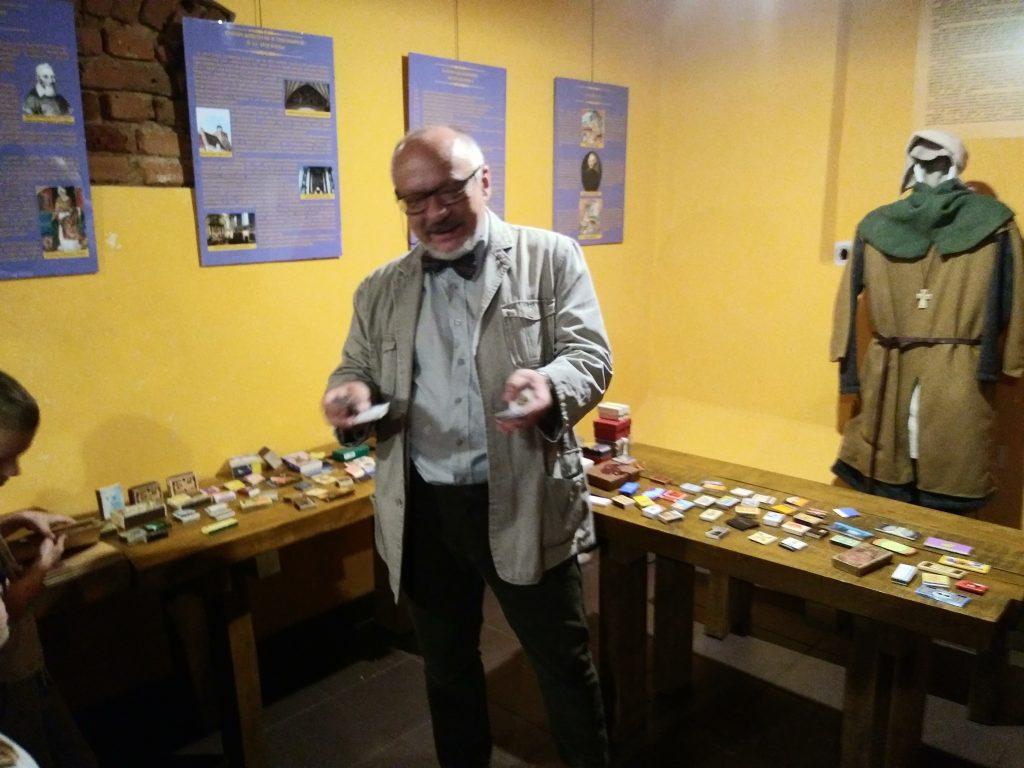 Stojąca osoba na tle stołów z kolekcją pudełek po zapałkach, z tyłu widoczny manekin w stroju średniowiecznym, na ścianie wiszące tablice