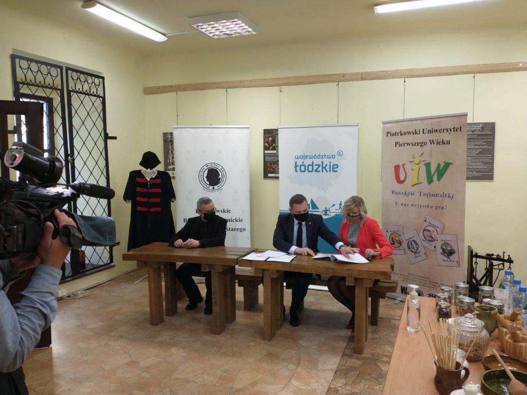 Trzy siedzące osoby za stołem na tle rollupów podpisujące dokument, z boku widoczny fragment kredensu
