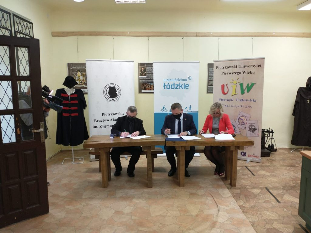 Trzy siedzące osoby za stołem na tle rollupów podpisujące dokument