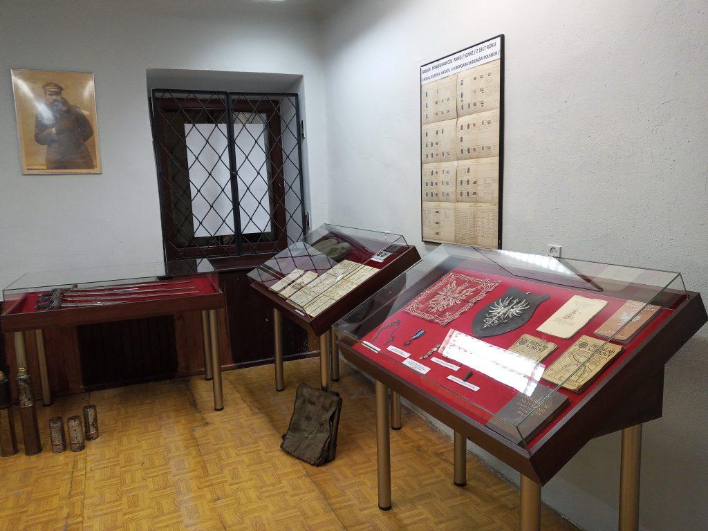 Zdjęcie przedstawia trzy gabloty wystawiennicze z pamiątkami legionowymi