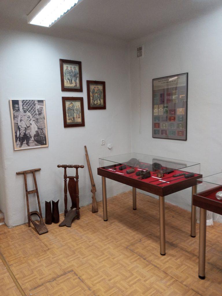 Zdjęcie przedstawia gablotę wystawienniczą z pamiątkami legionowym, wiszące na ścianach fotografie, obrazy oraz tablice o tematyce legionowej, a także przyrządy pomagające ubierać buty wojskowe