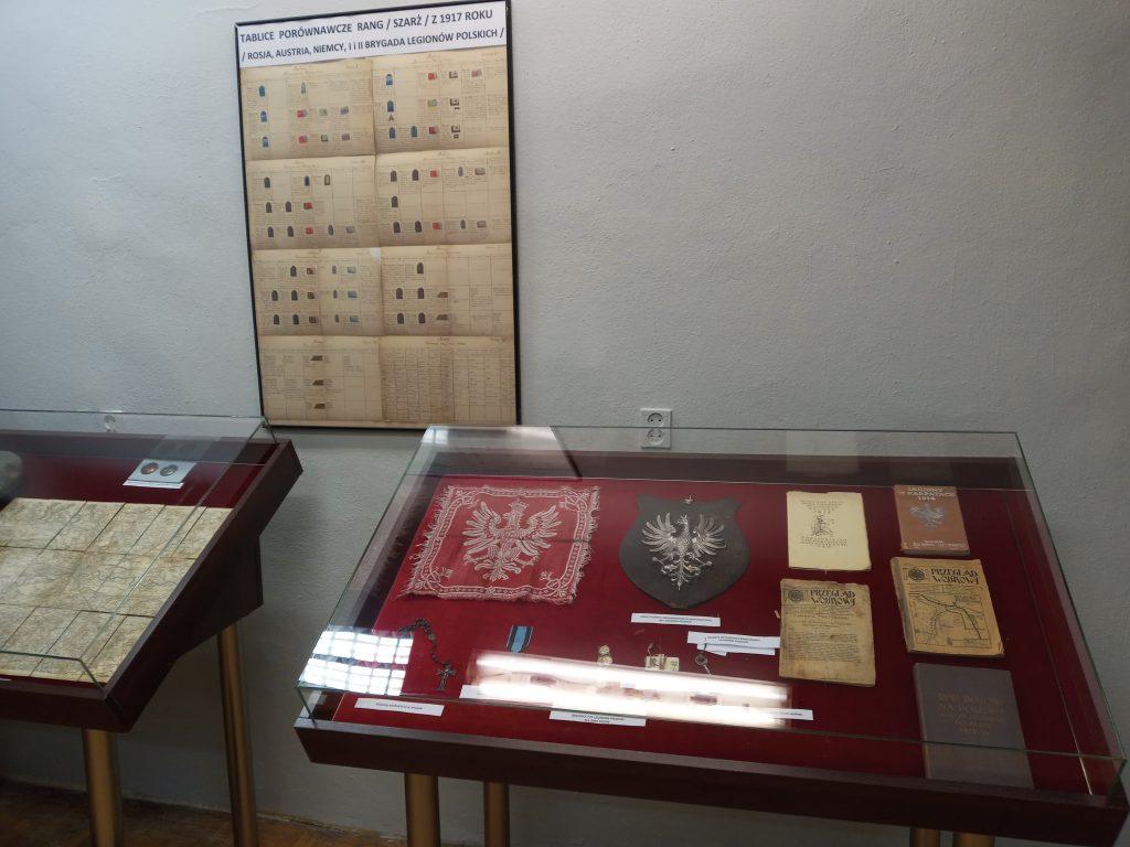 Zdjęcie przedstawia dwie gabloty wystawiennicze z pamiątkami legionowymi oraz wiszącą na ścianie tablicę