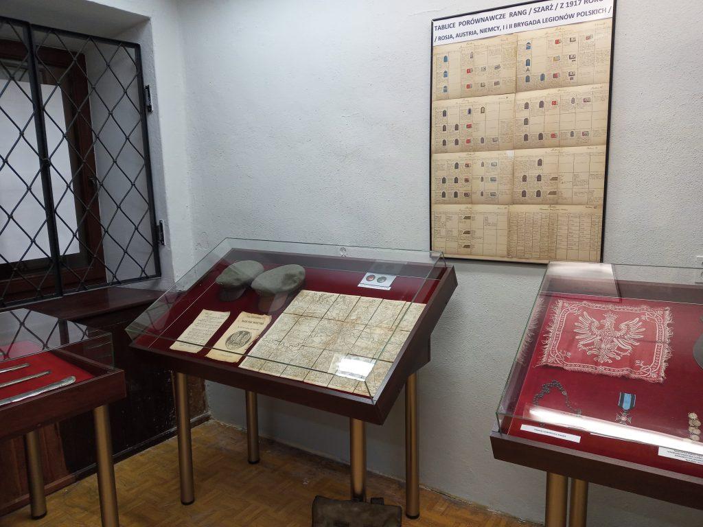 Zdjęcie przedstawia trzy gabloty wystawiennicze z pamiątkami legionowymi oraz wiszącą na ścianie tablicę