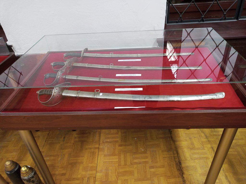 Zdjęcie przedstawia gablotę z bronią białą – czterema szablami
