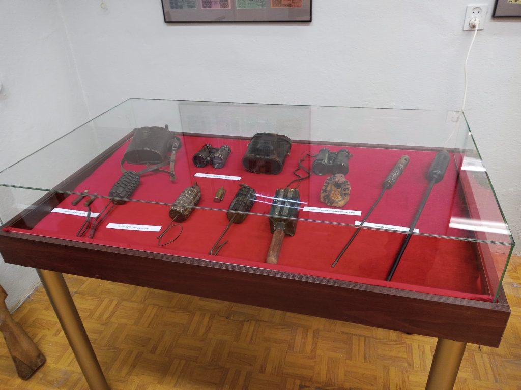 Zdjęcie przedstawia gablotę z uzbrojeniem oraz z lornetkami